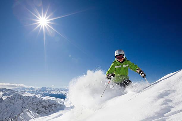 glücklich weibliche skifahrer mit blick auf die berge - skirennen stock-fotos und bilder