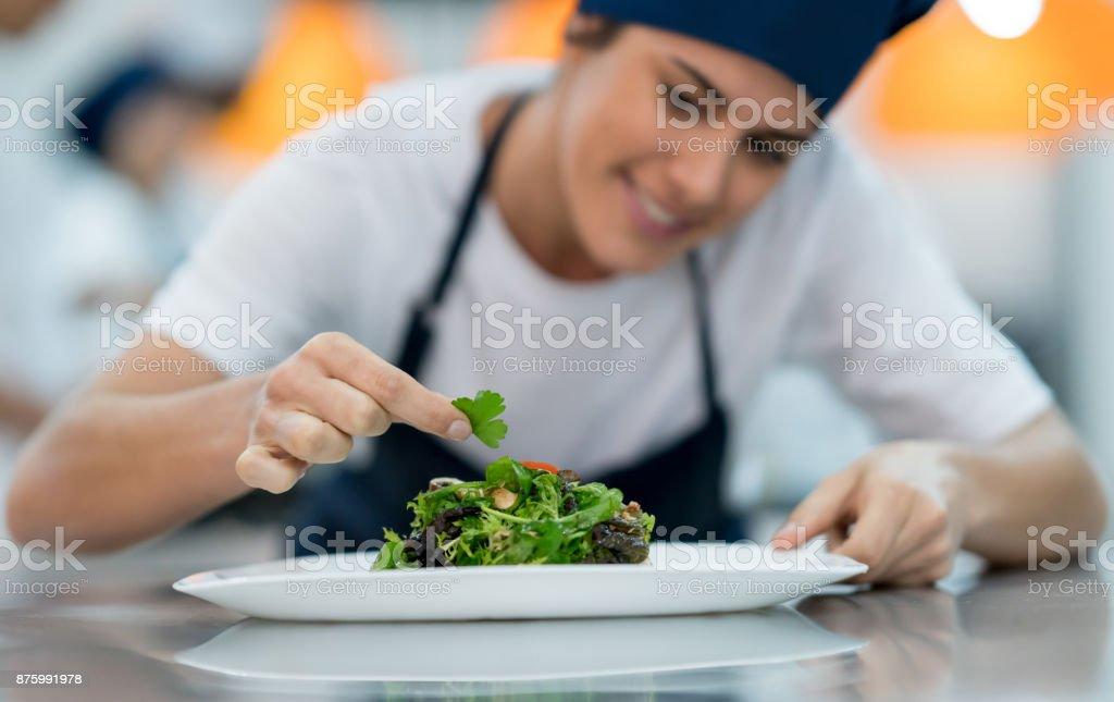 Feliz sub-chef feminino acrescentando detalhes para uma salada deliciosa - foto de acervo