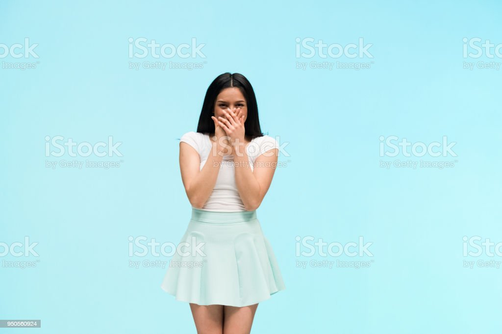 Happy female standing in front of blue background stock photo