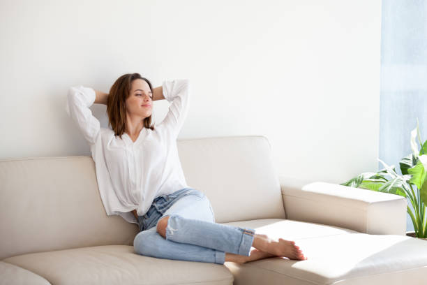 Happy female stretching on cozy coach spending weekend at home Happy young woman enjoying sunny morning lying on cozy sofa in modern apartment, smiling female relaxing on couch planning day off, calm girl stretching on couch resting and spending weekend at home relaxation stock pictures, royalty-free photos & images