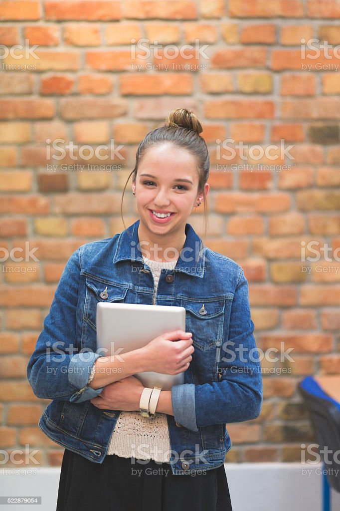 Happy female student at school, laughing at camera Portrait of happy asian student holding notebooks and laughing at camera. Adult Stock Photo
