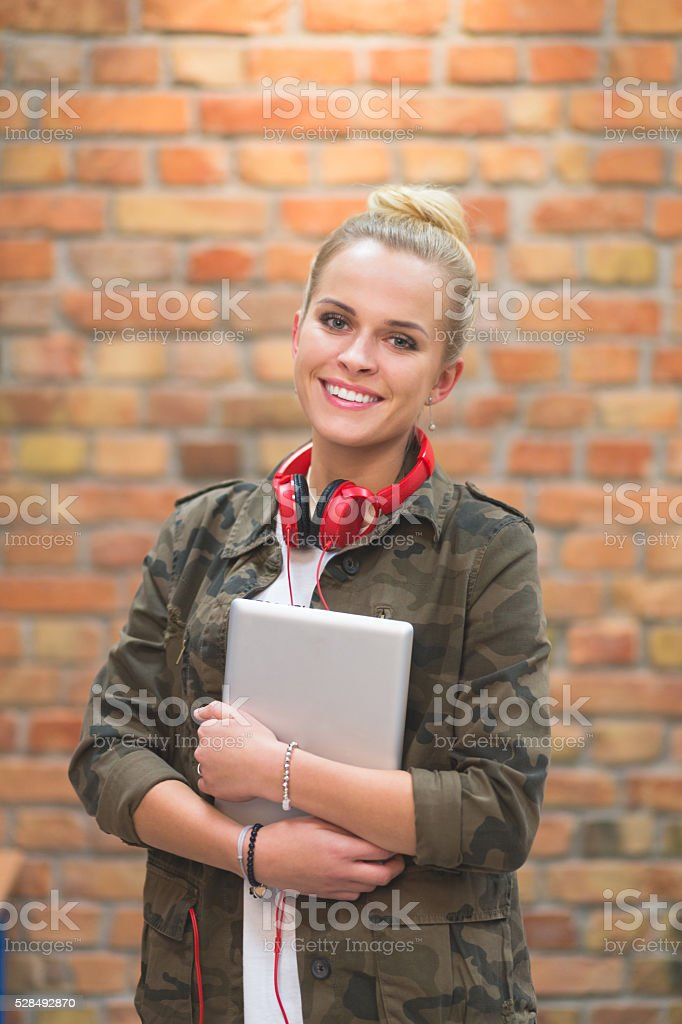Happy female student at school, laughing at camera Portrait of happy student holding notebooks and laughing at camera, standing in front of brick wall. Achievement Stock Photo