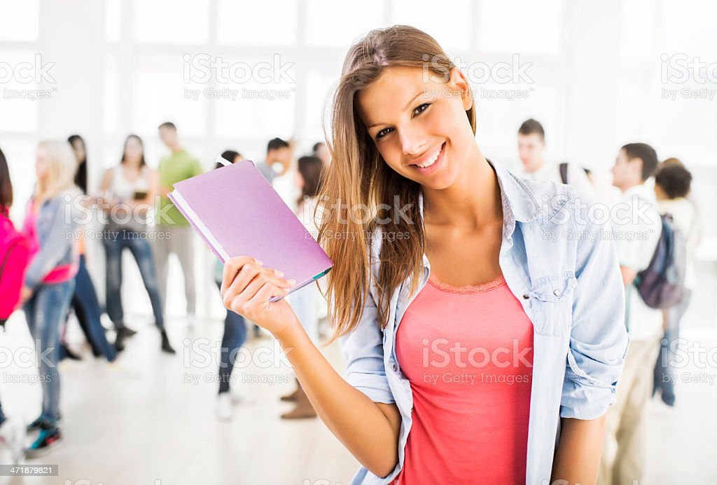Happy female student holding a book. royalty-free stock photo