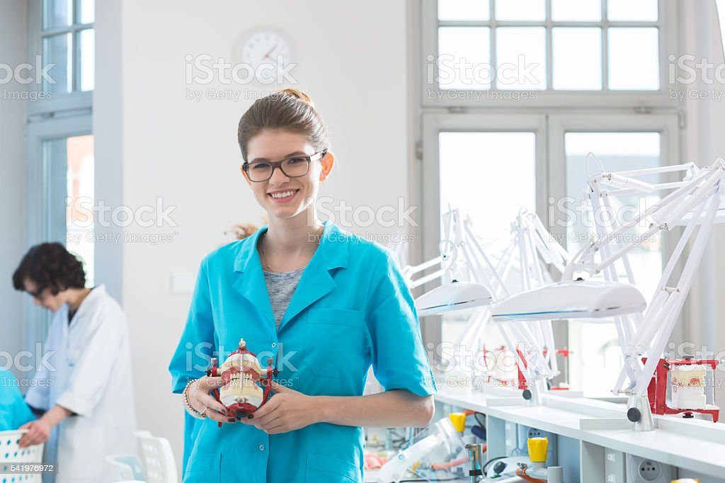 Happy female student holding denture stock photo