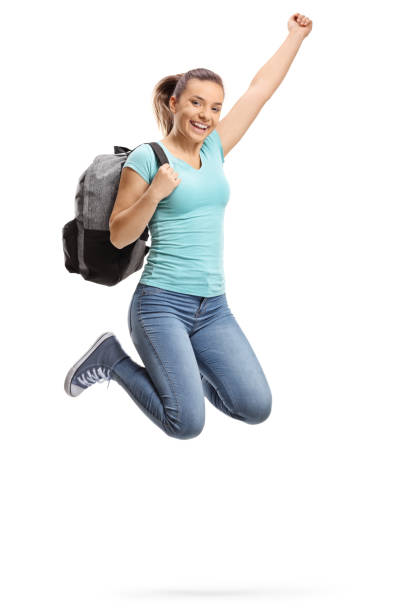 Happy female student jumping stock photo