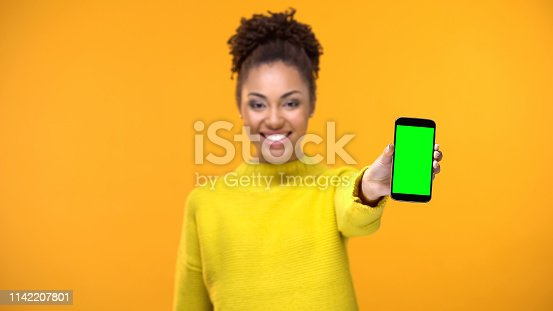 istock Happy female student showing smartphone with green screen, social network app 1142207801