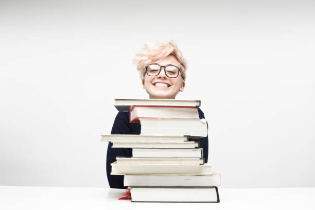 Happy Female Student Sitting Behind Pile of Textbooks stock photo