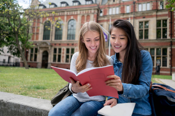 happy female students studying outdoors - uk travel stock photos and pictures