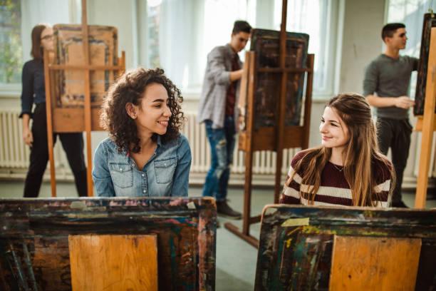 glücklich studentinnen sprechen bei der herstellung der gemälde im atelier. - high school bilder stock-fotos und bilder