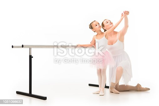 466300721 istock photo happy female teacher in tutu helping little ballerina exercising at ballet barre stand isolated on white background 1051098632