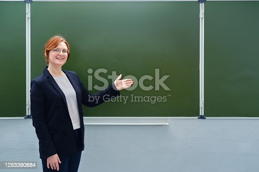 639569206 istock photo Happy female teacher smiles next to an empty blackboard, copy space for text. A young teacher in glasses and a jacket stands at the blackboard in a school classroom 1253390884