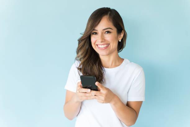 Feliz mujer mensajes de texto en el teléfono móvil en el estudio - foto de stock
