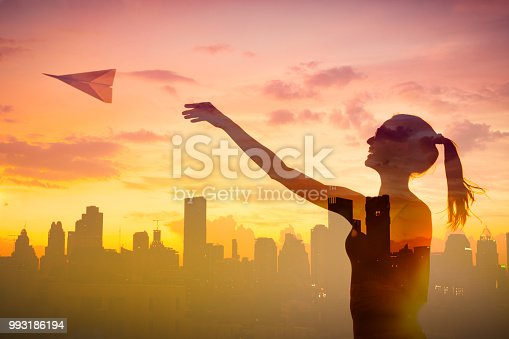istock Happy female throwing paper airplane against city background. 993186194