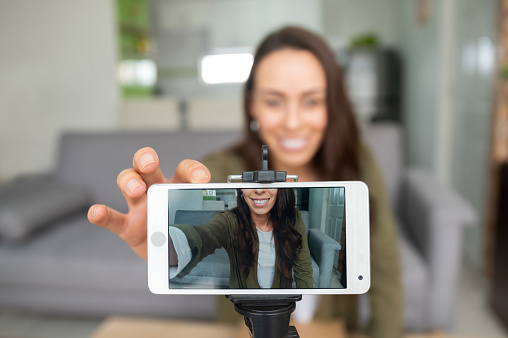 Happy female vlogger recording content at home using her cell phone while staying at home - lifestyle concepts