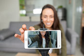 istock Happy female vlogger recording content at home using her cell phone 1266103790