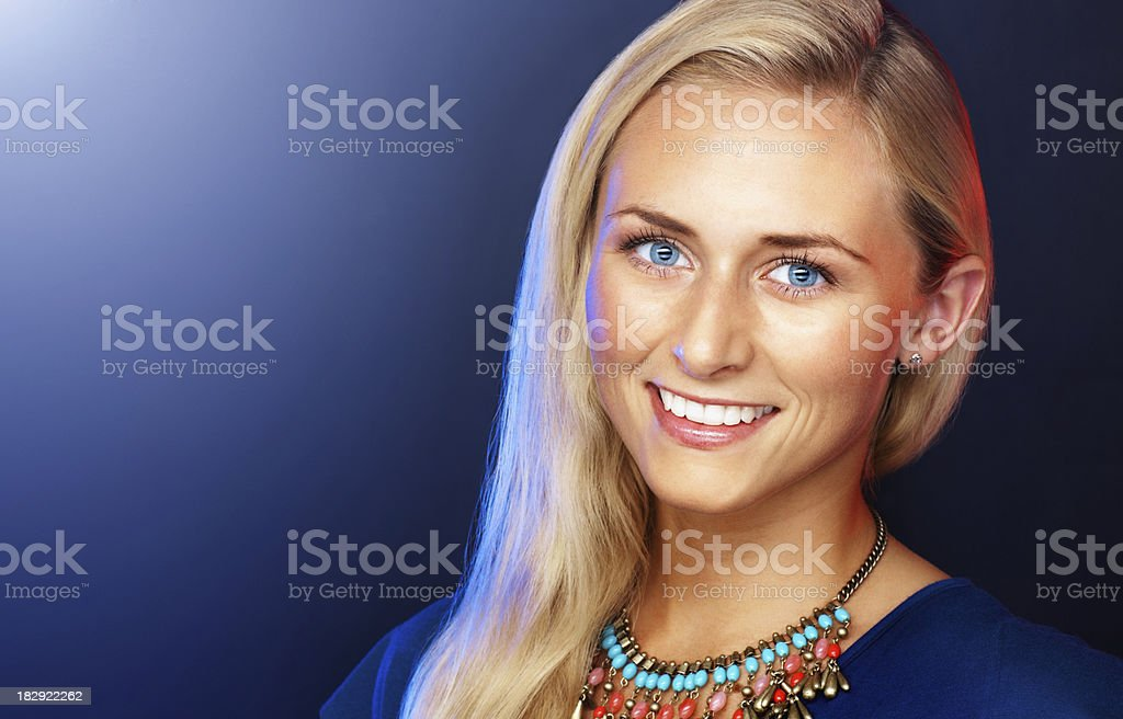 Happy female wearing necklace against colored background royalty-free stock photo