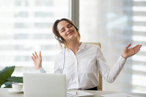 Happy female worker enjoying favorite music at work stock photo