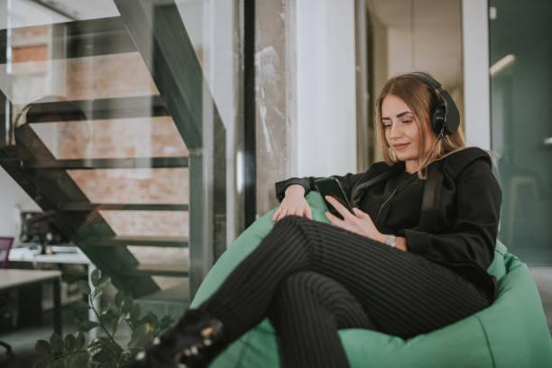 glücklich arbeitnehmerin lieblings musik bei der arbeit zu genießen - geräusche app stock-fotos und bilder