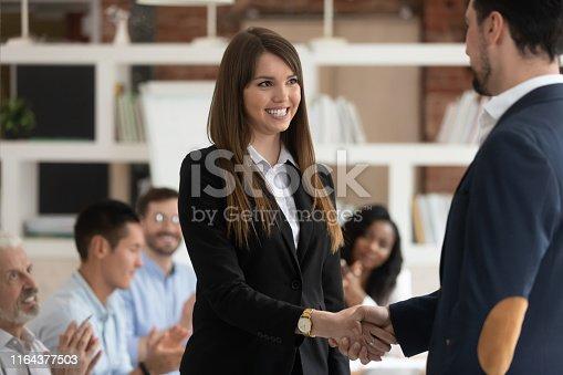 istock Happy female worker get rewarded for good work handshake boss 1164377503
