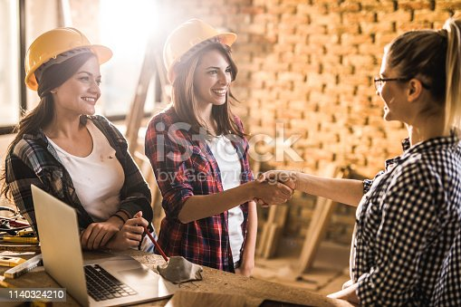 968825926istockphoto Happy female workers shaking hands with architect at construction site. 1140324210