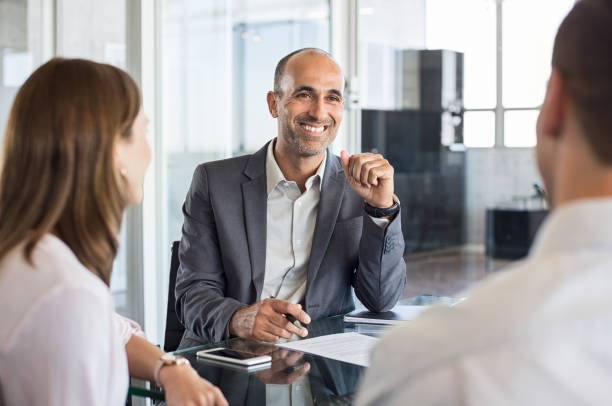 Happy financial agent smiling Mature financial agent in meeting sitting with young couple. Happy consultant talking with couple about their savings plan. Insurance advisor in a meeting with man and woman. salesman stock pictures, royalty-free photos & images