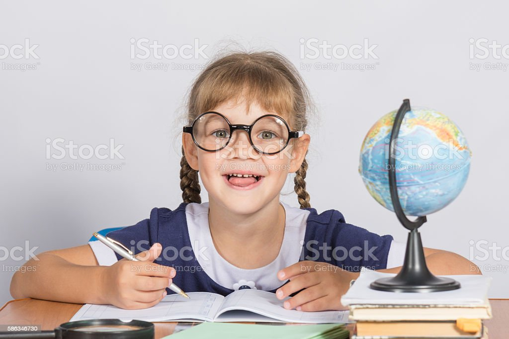 Happy first grader sits at a table in the classroom stock photo