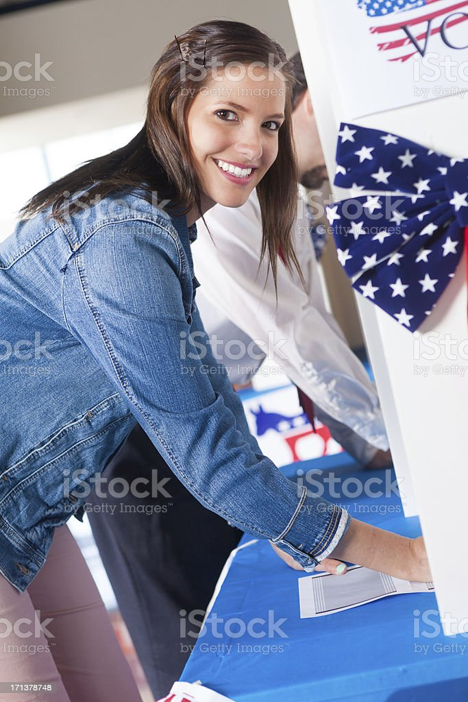Happy first time voter choosing candidate at voting election center royalty-free stock photo