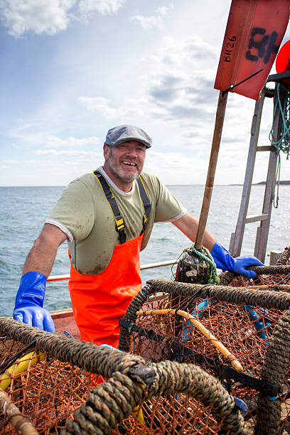 Happy Fisherman A happy fisherman smiles at the camera as he stands on his fishing boat. His lobster crate are propped up in front of him ready to be thrown into the sea. fisherman stock pictures, royalty-free photos & images
