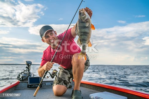istock Happy fisherman with big perch fish trophy at boat 1132922987