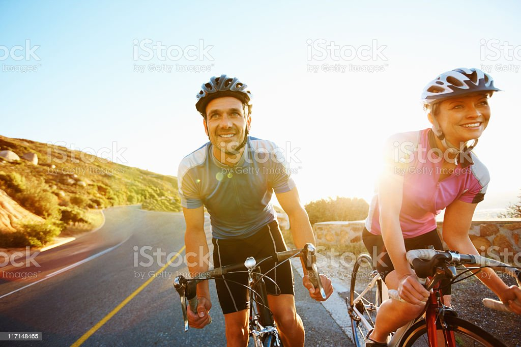 A happy fit couple riding their bicycles stock photo