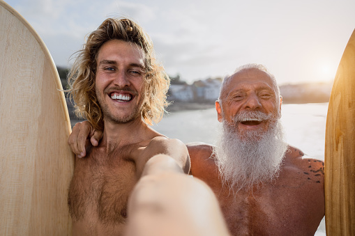 Happy fit surfers taking selfie while having fun surfing together at sunset time - Extreme sport lifestyle and friendship concept