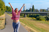 Happy fit young woman cheering and celebrating as she walks along a river after working out jogging