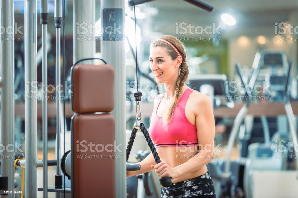 Happy cabe mulher vestindo sutiã rosa aptidão durante o exercício de extensão de tríceps corda cabo - Foto de stock de Academia de ginástica royalty-free