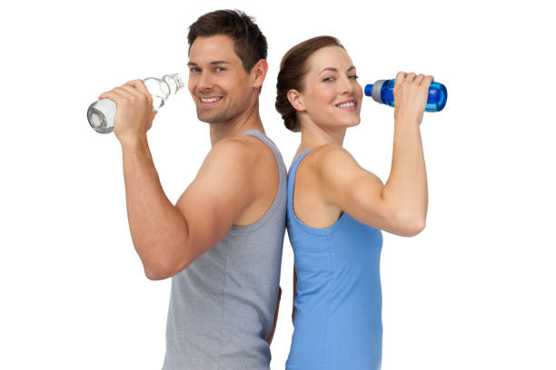 Happy fit young couple with water bottles stock photo