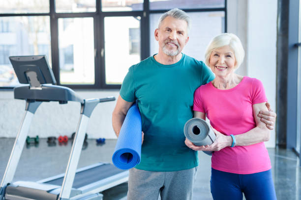 Happy fitness couple holding yoga mats and smiling at camera in gym - foto stock