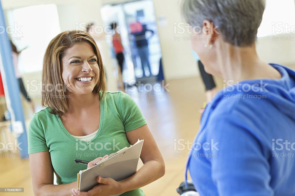 Happy fitness instructor checking in senior student for exercise class royalty-free stock photo