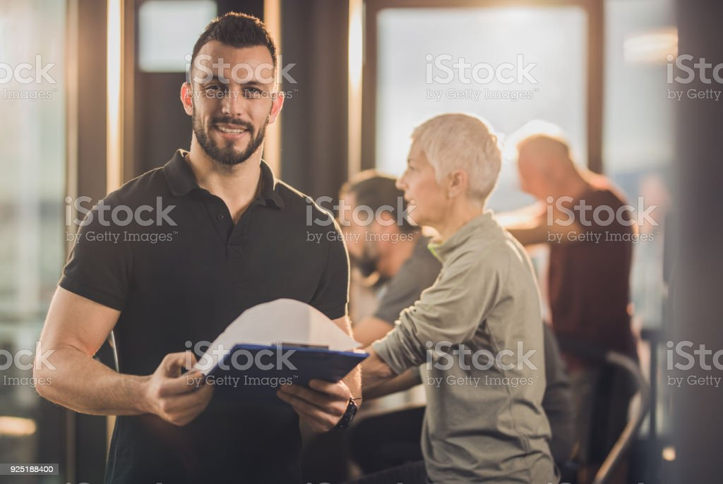 Happy fitness instructor with training plan in a health club. stock photo
