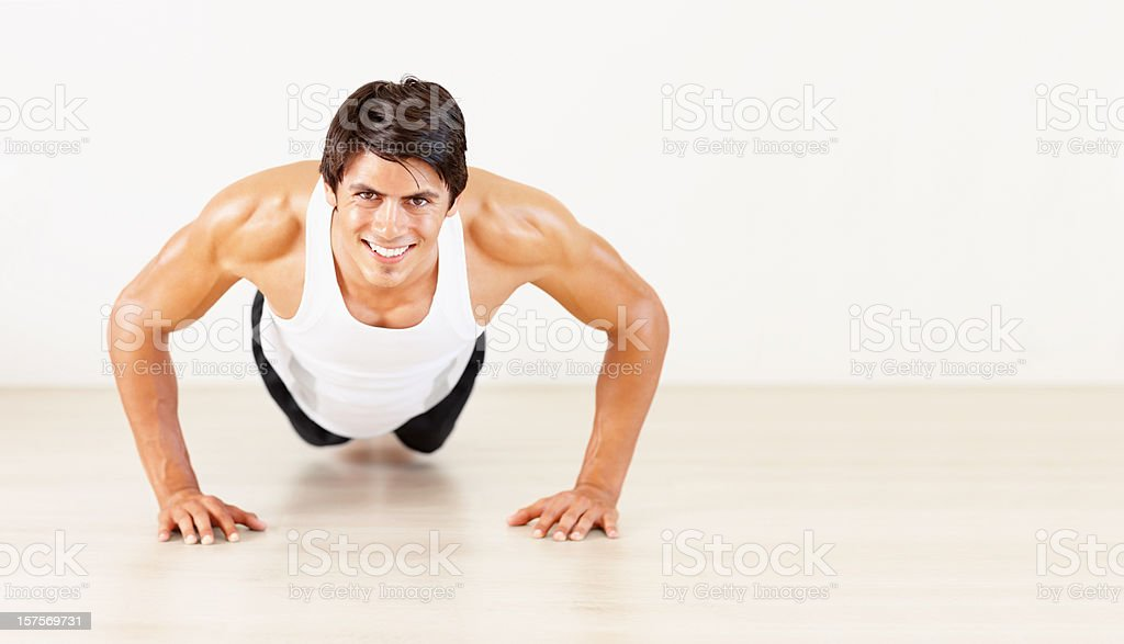 Happy fitness man doing push ups at a gym royalty-free stock photo