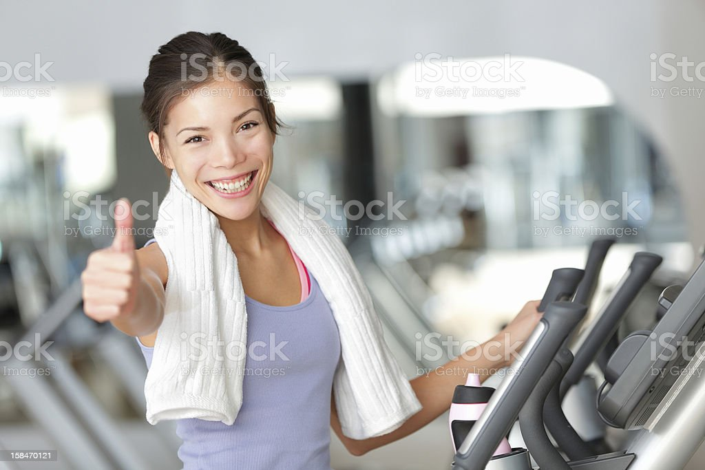 Happy fitness woman thumbs up in gym stock photo