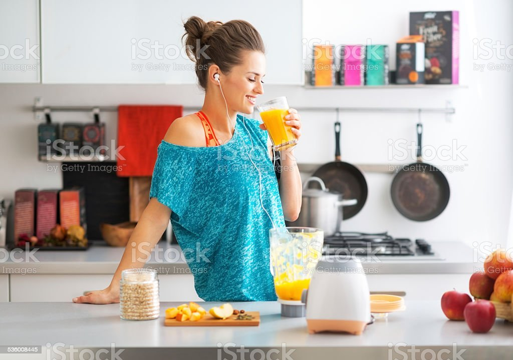 happy fitness young woman drinking pumpkin smoothie in kitchen stock photo