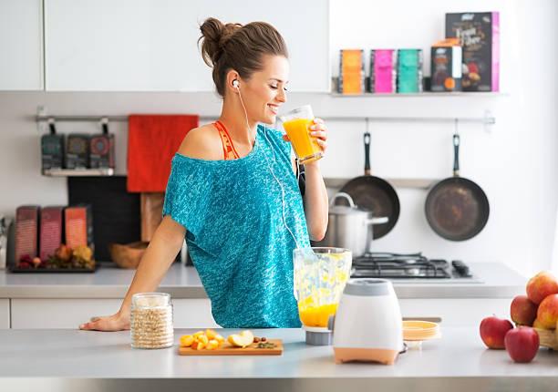happy fitness junge frau trinken smoothie in küche kürbis - diät shakes stock-fotos und bilder