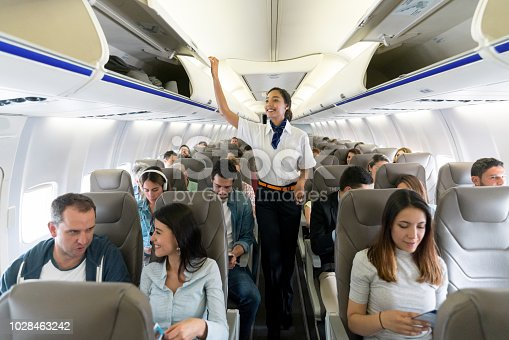 Happy flight attendant walking the aisle in an airplane closing overhead compartments and smiling - travel concepts