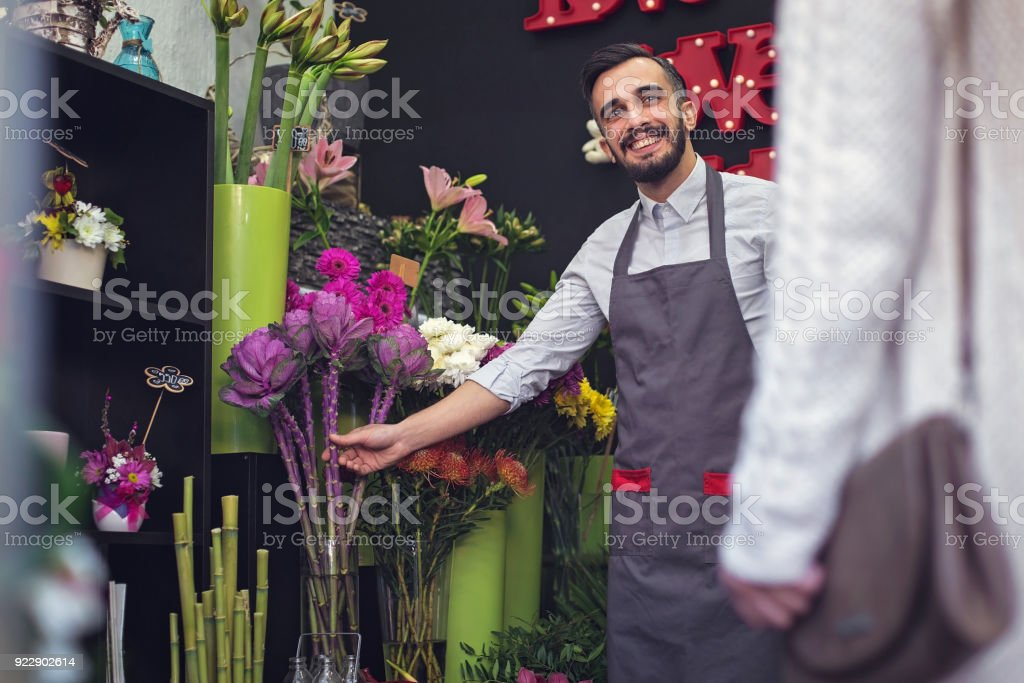 Happy florist selling flowers foto stock royalty-free