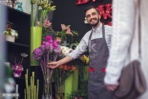 istock Happy florist selling flowers 922902614