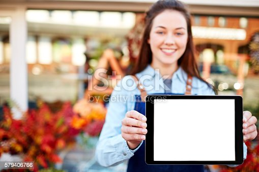 863476166istockphoto Happy florist showing digital tablet with blank screen 579406766