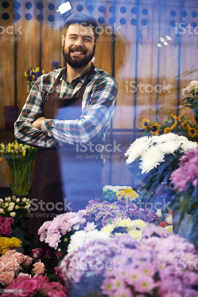 Happy flower shop owner smiling at camera through shop window