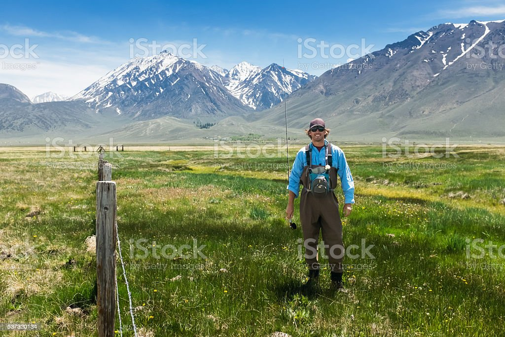 Happy Fly Fisherman Smiling In A Mountain Meadow stock photo