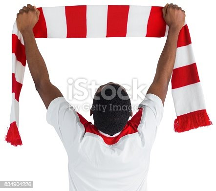 istock Happy football fan waving scarf 834904226