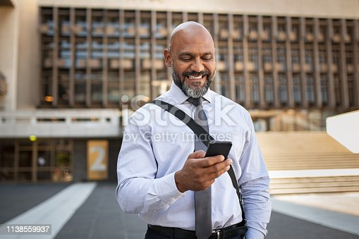 istock Happy formal businessman using phone on street 1138559937