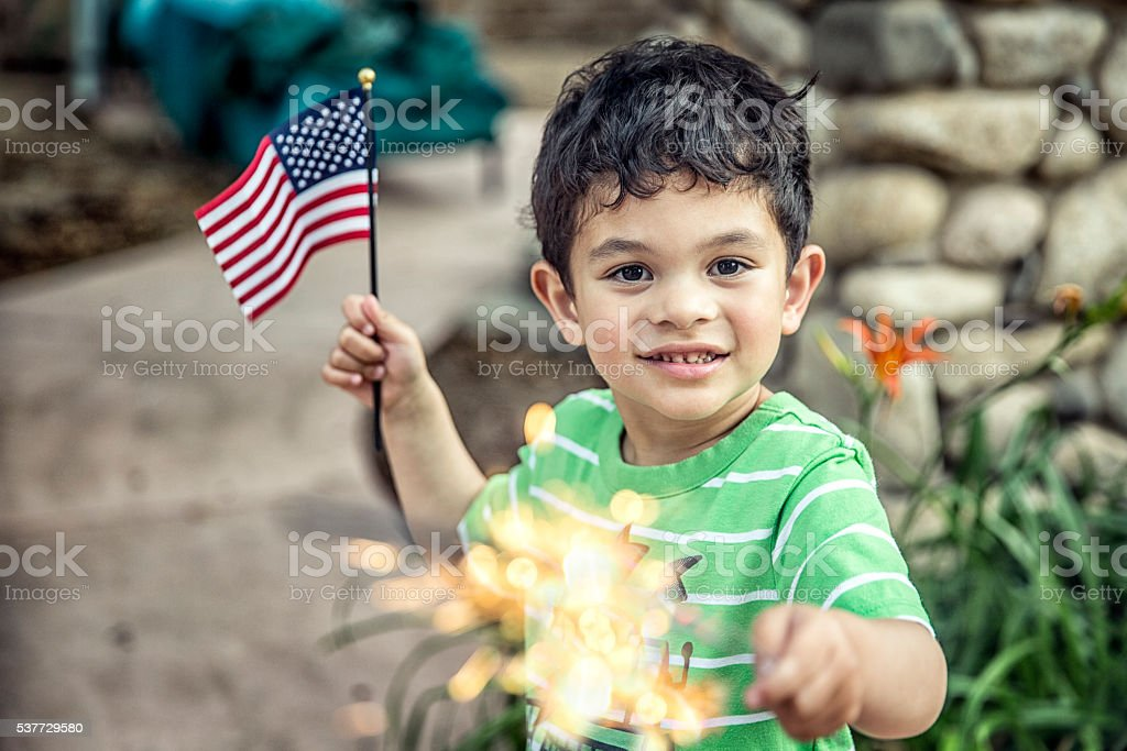 Small boy holding a sparkler and a American flag
